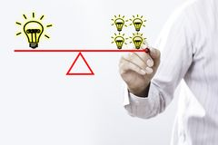 Businessman hand drawing many ideas small bulb equal a one big b. Ulb, Balance concept stock photo