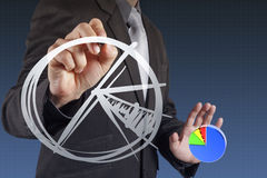 Businessman hand drawing a pie chart Stock Image