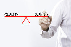 Businessman hand drawing Quality and Quantity balance - Business royalty free stock photo