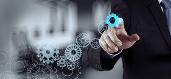 Businessman hand draws gear to success