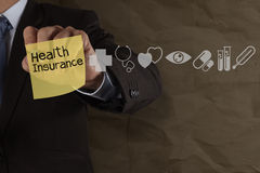 Businessman hand draws health insurance with sticky note and med Stock Photo