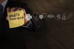 Businessman hand draws health insurance with sticky note and med Royalty Free Stock Photo