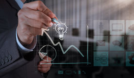 Businessman hand draws lightbulb with new computer interface. As solution business concept Royalty Free Stock Images