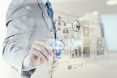 Businessman hand draws lightbulb with new computer interface stock illustration