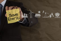 Businessman hand draws save energy on sticky note with icons and Royalty Free Stock Photos