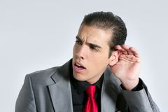 Businessman with hand in ear as a deafness sign Stock Photos