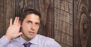 Businessman with hand on ear listening over wooden wall. Digital composite of Businessman with hand on ear listening over wooden wall Stock Photos