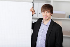 Businessman With Hand On Flip Chart. Young businessman with hand on flip chart in office royalty free stock photo