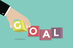 Businessman hand with GOAL cubic box puzzle Stock Photos