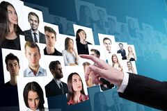 Social media and recruiting concept. Businessman hand going through candidate picture gallery on blue background. Social media and recruiting concept Stock Image
