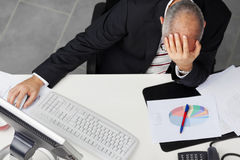 Businessman With Hand On Head At Desk Royalty Free Stock Photos