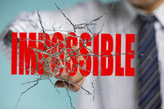 Businessman hand hitting red impossible word on cracked transpar Stock Images