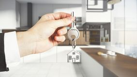 Lifestyle and real estate concept. Businessman hand holding abstract key with house keychain on blurry kitchen interior background. Lifestyle and real estate Royalty Free Stock Images