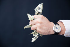 Businessman hand holding bills of US dollar in fist Stock Photos