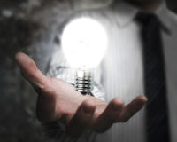 Businessman hand holding brightly light bulb illuminated dark Royalty Free Stock Photos