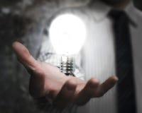 Businessman hand holding brightly light bulb illuminated dark Royalty Free Stock Photos