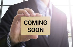 Businessman hand holding business card with message coming soon. Royalty Free Stock Images