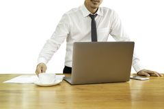 Businessman hand holding coffee cup with laptop on wooden desk in clipping path. stock photography
