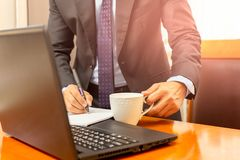 Businessman hand holding coffee cup and writing on notebook on wprking desk. royalty free stock photo
