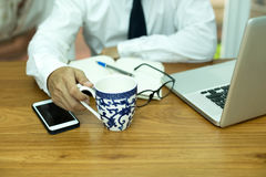 Businessman hand holding coffee mug with cell phone and notebook. In office Royalty Free Stock Images