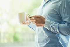 Businessman hand holding coffee and reading phone royalty free stock photos