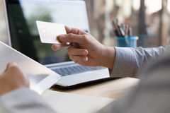 Businessman hand holding a Credit card intent to made a online p. Businessman doing online banking, making a payment or purchasing goods on the internet entering stock image
