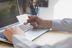 Businessman hand holding a Credit card intent to made a online p. Businessman doing online banking, making a payment or purchasing goods on the internet entering royalty free stock images