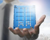 Businessman hand holding 3d blue cargo container. With sun clouds sky cityscape background Stock Photos