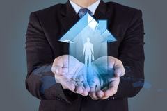 Businessman hand holding 3d house. With human icon as insurance concept royalty free stock image