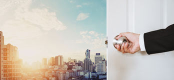 Businessman hand holding door knob opening, with Bangkok cityscape in sunrise Royalty Free Stock Photos