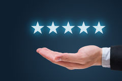 Businessman hand holding five stars isolated on blue background.  Royalty Free Stock Photo