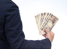 Businessman hand holding Japanese banknote. Businessman hands holding Japanese banknote Royalty Free Stock Photography