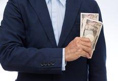Businessman hand holding Japanese banknote. On white background Royalty Free Stock Photo