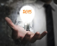 Businessman hand holding 2015 light bulb illuminated dark Stock Photos