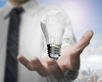 Businessman hand holding lightbulb with wind turbines inside Royalty Free Stock Photo