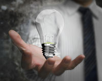Businessman hand holding lightbulb with wind turbines inside Stock Photo