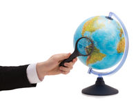 Businessman hand holding magnifier over globe Stock Photography