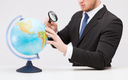 Businessman hand holding magnifier over globe Stock Images