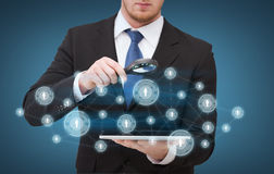 Businessman hand holding magnifier over tablet pc Stock Photos