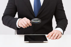 Businessman hand holding magnifier over tablet pc Stock Photography