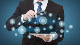 Businessman hand holding magnifier over tablet pc Royalty Free Stock Photography