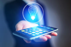 Businessman hand holding mobile phone with bulb idea icon. View of a Businessman hand holding mobile phone with bulb idea icon Stock Image