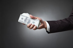 Businessman hand holding money on dark background Stock Image