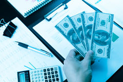 Businessman hand holding money on working desk. Royalty Free Stock Photography