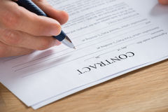 Businessman Hand Holding Pen On Contract Paper Stock Photo