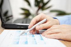 Businessman hand holding pen over business analyze with laptop c Stock Image