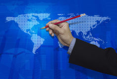 Businessman hand holding a pencil over blue digital world map ba Stock Photography