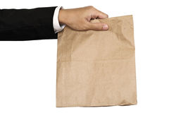 Businessman hand holding(Sharing,giving) brown paper bag lunch, isolated on white background Royalty Free Stock Photos