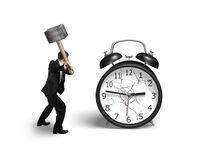 Businessman hand holding sledgehammer hitting alarm clock with b Stock Photos