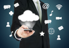 Businessman hand holding smart phone cloud connectivity. On drak background Royalty Free Stock Images